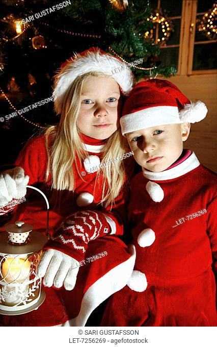 Children and Christmas. Girl and boy wearing brownie's caps