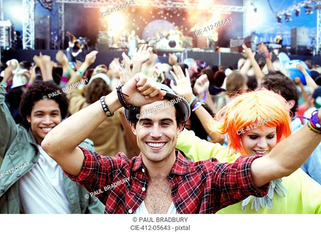 Portrait of fans dancing and cheering at music festival