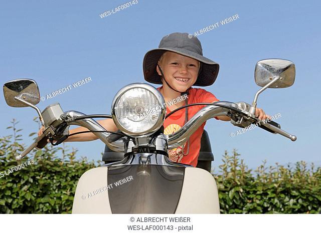 Happy boy on motor scooter