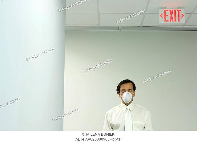 Man under exit sign wearing pollution mask, eyes closed