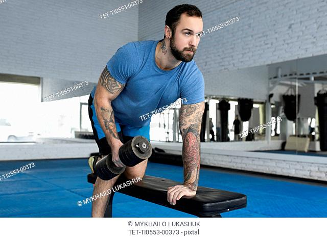 Mid adult man lifting dumbbell in gym