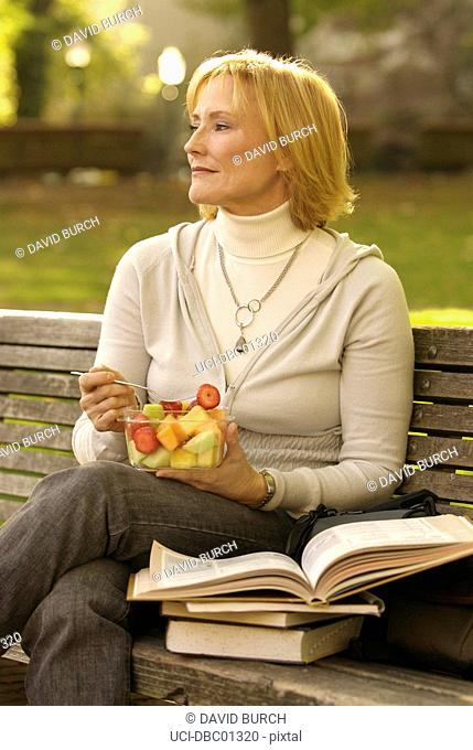 Woman eating fruit salad and reading book