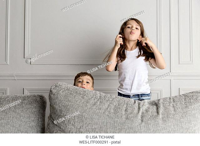 Two little children pulling funny faces behind the couch