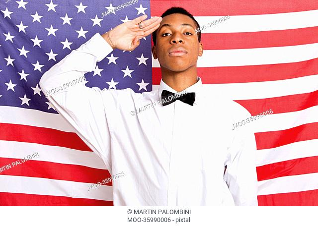 Portrait of young man saluting against American flag