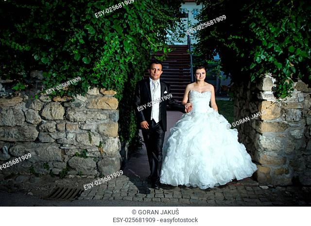 Newlyweds holding hands and walking between stone walls and treetops wile looking at the camera