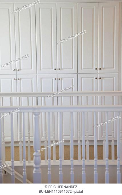 Close-up of white railings and cabinets along hallway at home