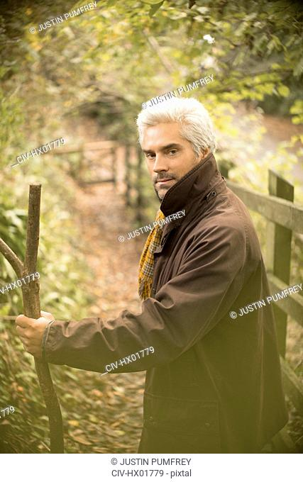 Portrait serious man with walking stick on autumn path