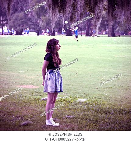 Young woman, 19 years old, standing alone on playing field