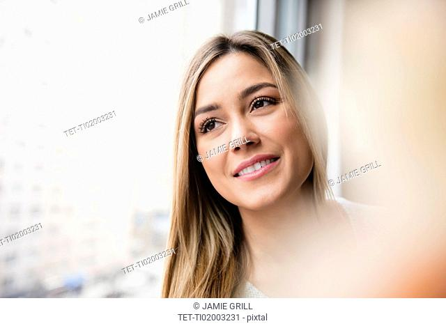 Portrait of young woman looking through window