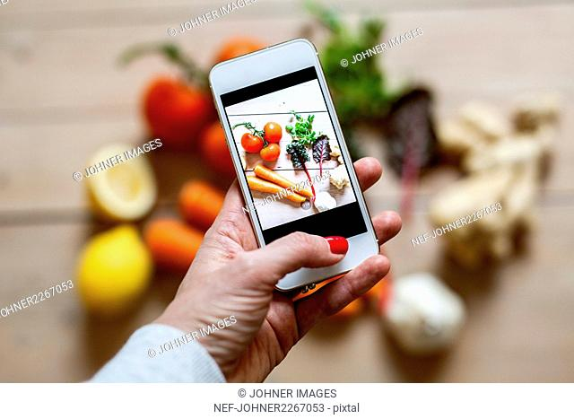 Woman photographing vegetables with smartphone