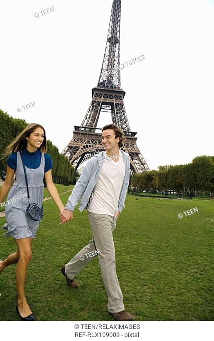 Young couple walking in park with Eiffel tower in background, Paris, France