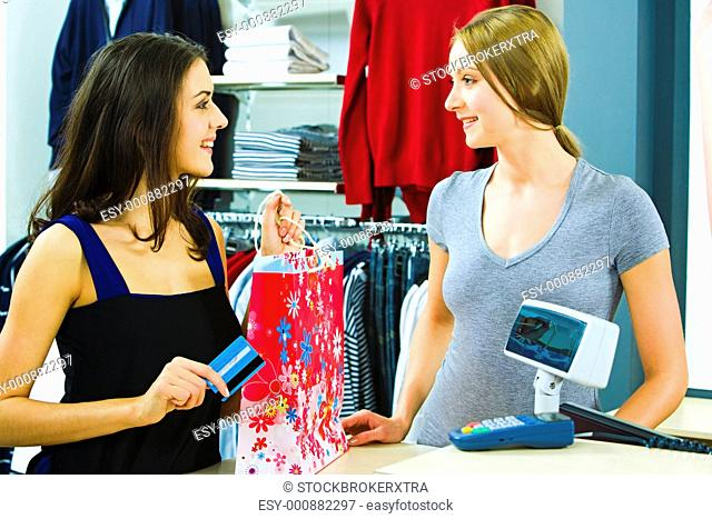 Portrait of a buyer and a shop assistant looking at each other with smiles by the pay desk in the clothing department