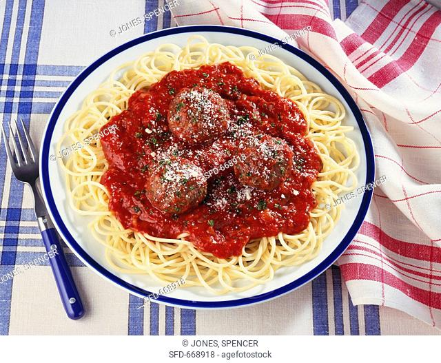 Plate of Spaghetti and Meatballs on Blue and White Table Cloth, Fork