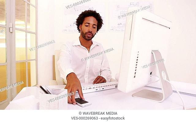 Businessman texting on the phone at his desk