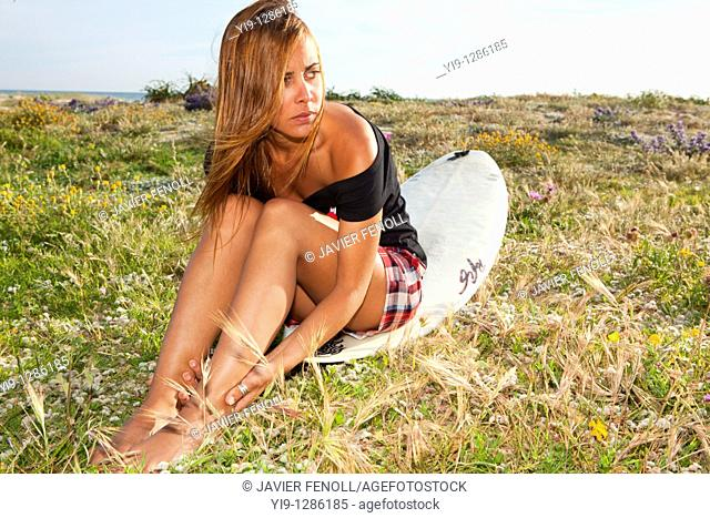 Young woman posing with surfboard