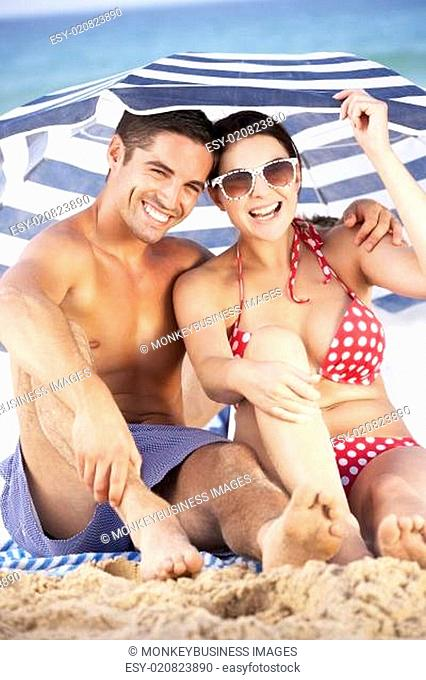 Couple Sheltering From Sun Under Beach Umbrella