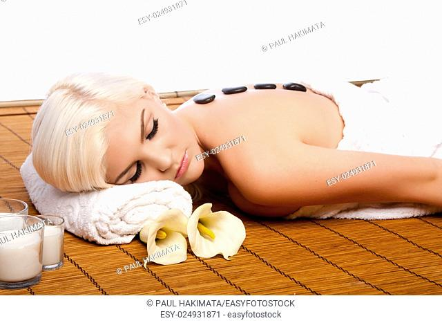 Beautiful young woman relaxing at spa getting therapeutic pampering lastone therapy