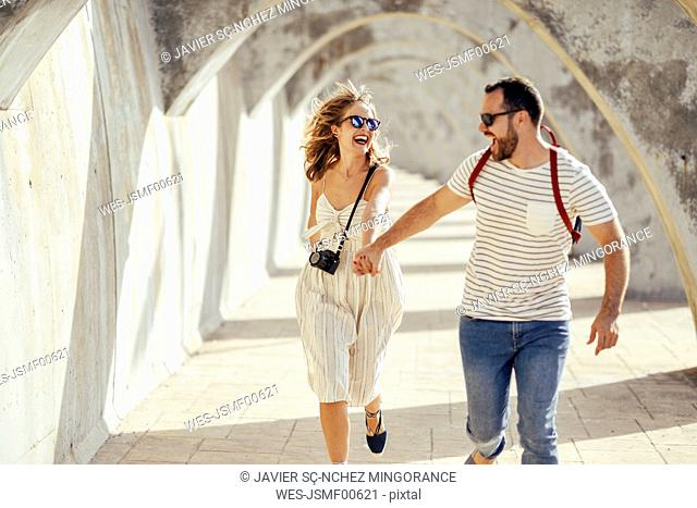 Spain, Andalusia, Malaga, carefree tourist couple running under an archway in the city