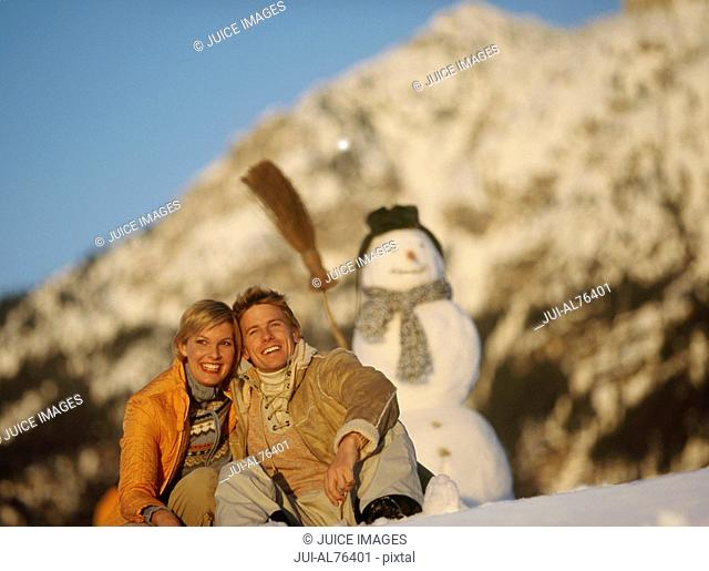 View of a young couple sitting in front of a snowman
