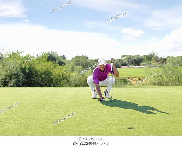 Hispanic golfer crouching on golf course