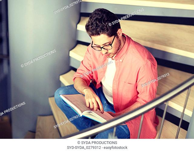 student boy or young man reading book at library