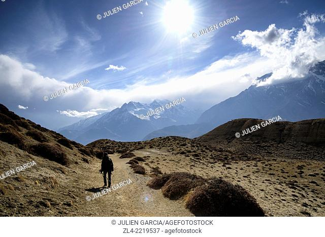 Trekker and mountains between the villages of Tangge and Chuksang. Nepal, Gandaki, Upper Mustang (near the border with Tibet). Model Released