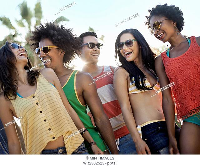 A group of friends, men and women hanging out together, partying