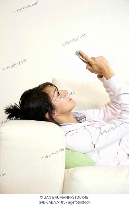 Woman with smartphone lying on couch, Munich, Bavaria, Germany