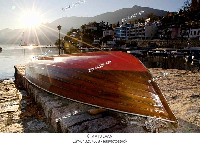 Boat lying upside down in sunset with sunbeam on an alpine lake maggiore in ascona switzerland