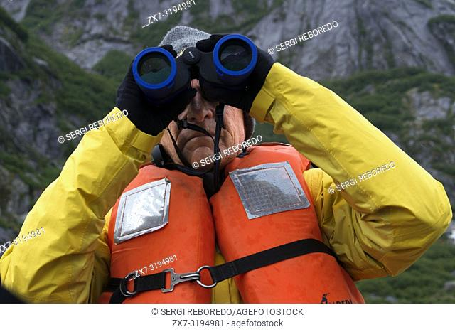 Passenger with binoculars on cruise ship Safari Endeavour at anchor at Fords Terror, Endicott Arm, Tongass National Forest, Juneau, Alaska, USA