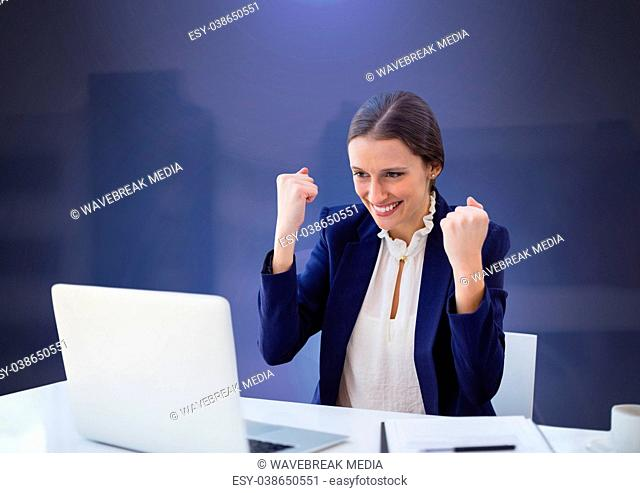 Businesswoman working on laptop celebrating success