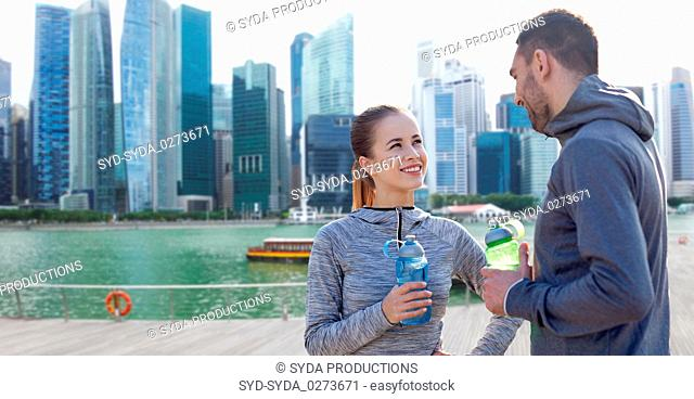 couple with bottles of water over singapore city