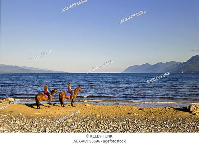 Two young women enjoy a fantastic view while horesback riding at a beach near Powell river on the upper Sunshine coast, Vancouver and coast mountain region