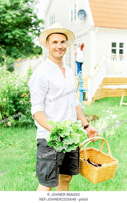 Man with basket and fresh vegetables in garden