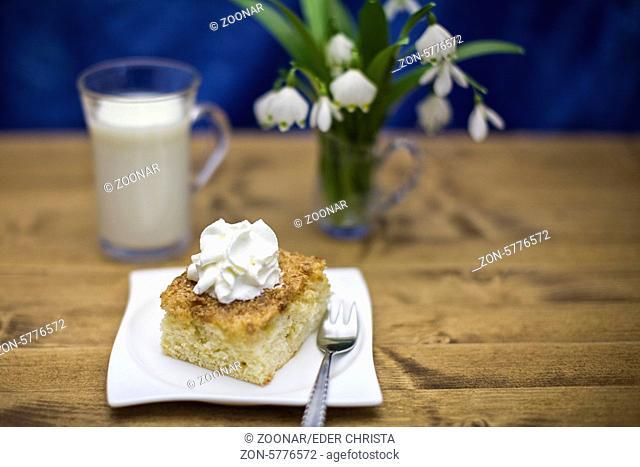 Buttermilchkuchen mit Sahnetuff und einem Glas Buttermilch