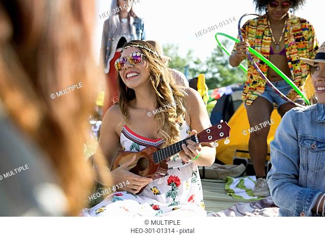 Young woman playing ukulele at summer music festival campsite
