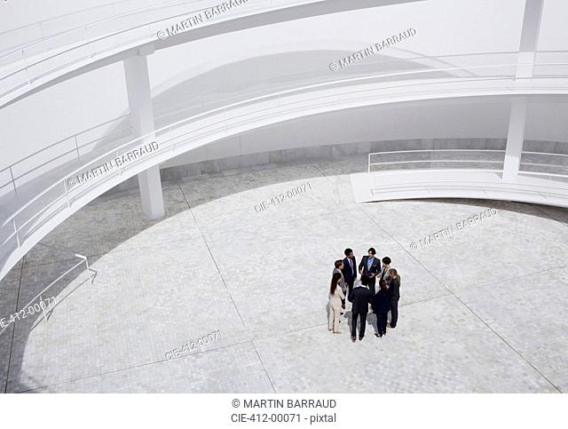 Business people standing in circle of modern courtyard