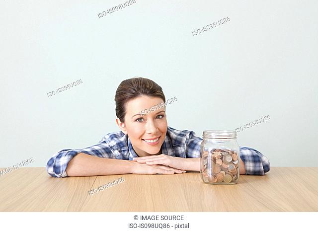 Young woman with jar of coins
