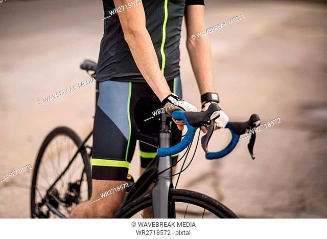 Athlete standing with his bicycle