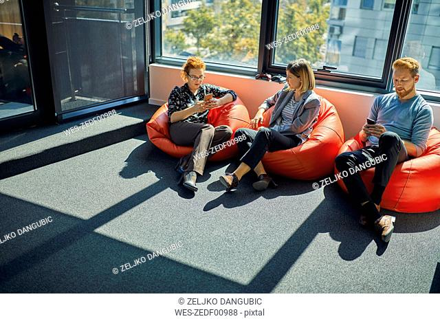 Colleagues with cell phones sitting in bean bags in office lounge