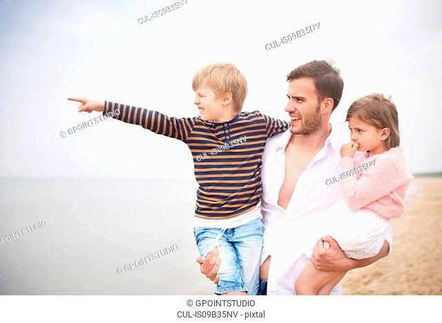 Father carrying children in arms on beach