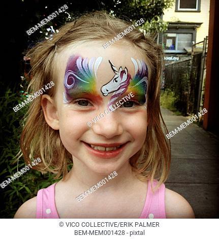 Caucasian girl wearing rainbow face paint
