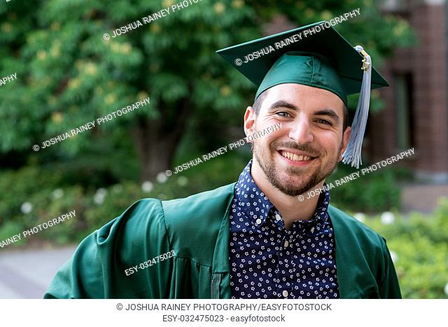 College senior poses for a graduation photo on campus in his cap and gown