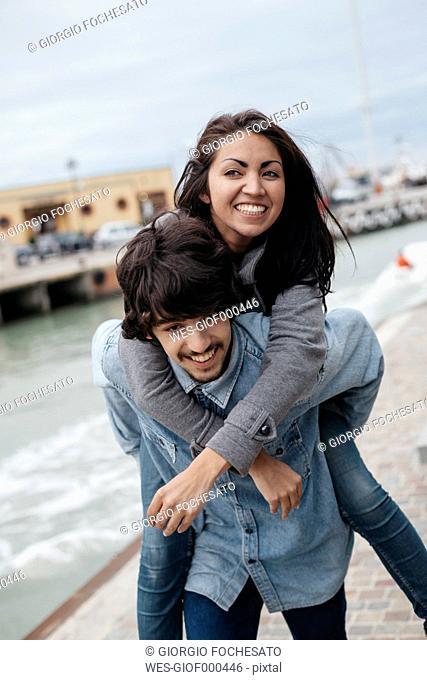 Italy, Rimini, young man carying girlfriend piggyback