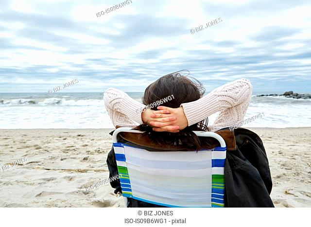 Rear view of woman looking out to sea from beach chair
