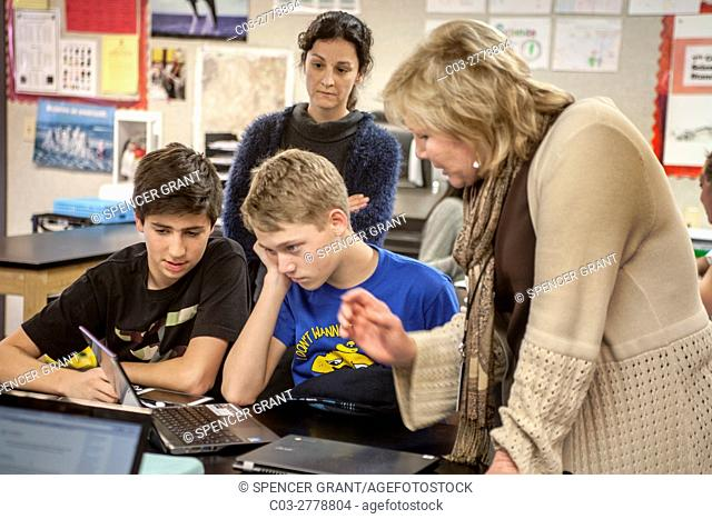 A perplexed Mission Viejo, CA, middle school science student gets assistance from a teacher as he gazes at a Google Chromebook laptop computer in STEM (Science