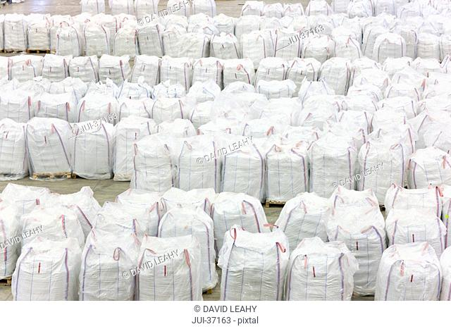 Large bags of recycled plastic pellets in warehouse