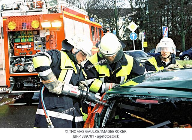 Firemen at traffic accident using Jaws of Life to rescue trapped car driver, Munich, Upper Bavaria, Bavaria, Germany