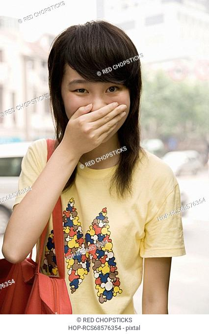 Portrait of a young woman covering her mouth with her hand