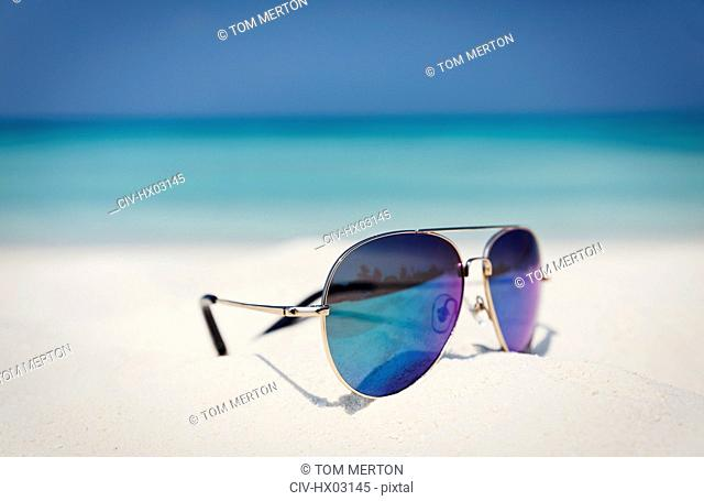 Close up aviator sunglasses in sand on sunny tropical ocean beach